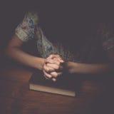 Kobieta wręcza modlenie z biblią, rocznika brzmienie zdjęcia royalty free