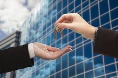 Kobieta Wręcza Nad kluczami przed Korporacyjnym budynkiem Fotografia Stock