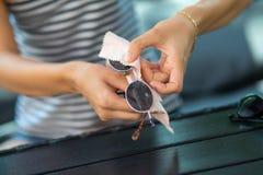 Kobieta wręcza obcierania słońca szkła z mikro włókna wytarciem zdjęcia stock