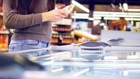 Kobieta wręcza otwierać szklanego drzwi w schładzającej sekci przy supermarketem i wybierać lody młode kobiety Zdjęcia Stock