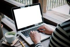 Kobieta wręcza pisać na maszynie na laptop klawiaturze z białymi pustego ekranu wi zdjęcia stock