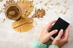Kobieta wręcza pisać na maszynie na telefonie komórkowym na wieśniaka stole z liśćmi i gorącą kawą na nim Zdjęcie Stock
