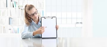 Kobieta wręcza pokazywać schowek z piórem, siedzi w biurowym biurku Zdjęcia Royalty Free