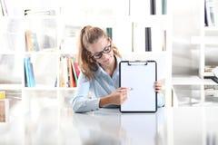 Kobieta wręcza pokazywać schowek z piórem, siedzi w biurze Obrazy Royalty Free