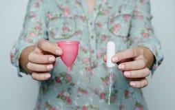 Kobieta wręcza porównywać menstrual filiżankę z tamponem Fotografia Stock
