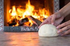 Kobieta wręcza robić świeżemu surowemu ciastu dla pizzy lub chleba pieczenia na drewnianym stole przeciw Płonącej grabie wygoda n Obrazy Stock