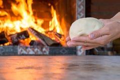 Kobieta wręcza robić świeżemu surowemu ciastu dla pizzy lub chleba pieczenia na drewnianym stole przeciw Płonącej grabie wygoda n Fotografia Royalty Free