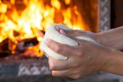 Kobieta wręcza robić świeżemu surowemu ciastu dla pizzy lub chleba pieczenia na drewnianym stole przeciw Płonącej grabie wygoda n Zdjęcie Stock