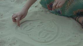 Kobieta wręcza rysunkowe śmieszne twarze na piasku na plaży zbiory