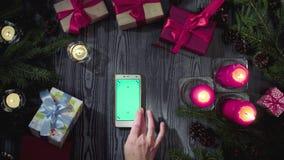 Kobieta wręcza scrolling mądrze telefon z zieleń ekranem zbiory