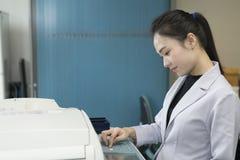 Kobieta wręcza stawiać prześcieradło papier w kopiowego przyrząd zdjęcia stock