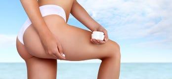 Kobieta wręcza stosować moisturizer śmietankę na udzie, odizolowywającym na morzu zdjęcia stock