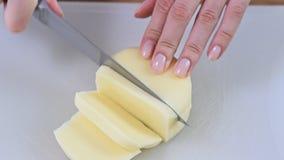 Kobieta wręcza tnącego mozzarella ser na drewnianej tnącej desce zbiory