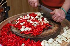 Kobieta wręcza tnących czerwonego chili pieprze i czosnku Fotografia Royalty Free