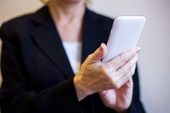 Kobieta wręcza trzymać białego telefon komórkowego zbliżenie Zdjęcia Stock