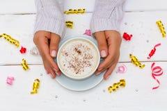 Kobieta wręcza trzymać filiżankę kawy na białym drewnianym stole Zdjęcia Royalty Free