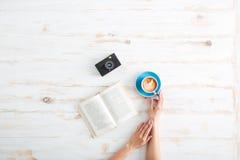 Kobieta wręcza trzymać filiżankę kawy nad drewnianym stołem Obraz Stock