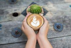 Kobieta wręcza trzymać filiżankę kawy nad drewnianym stołem, odgórny widok Zdjęcie Royalty Free