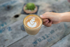 Kobieta wręcza trzymać filiżankę kawy nad drewnianym stołem, odgórny widok Obraz Stock