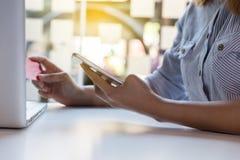 kobieta wręcza trzymać kredytową kartę i używać mobilnego mądrze telefon dla Zdjęcia Stock