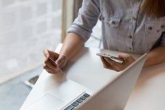 kobieta wręcza trzymać kredytową kartę i używać mobilnego mądrze telefon dla Obraz Royalty Free