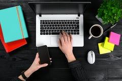 Kobieta wręcza trzymać mądrze i pisać na maszynie na klawiaturze laptop na czarnym drewnianym stole Zdjęcia Royalty Free