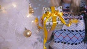 Kobieta wręcza trzymać prezent blisko choinki dekoracja nowego roku z bliska zbiory wideo