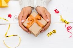 Kobieta wręcza trzymać prezenta pudełko na białym drewnianym stole Zdjęcie Royalty Free