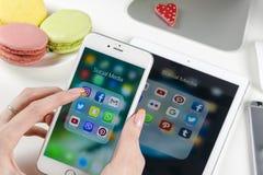 Kobieta Wręcza używać iphone 7 z ikonami ogólnospołeczny medialny facebook, instagram, świergot, Google zastosowanie na ekranie S Obraz Stock