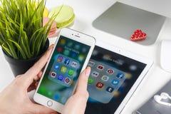 Kobieta Wręcza używać iphone 7 z ikonami ogólnospołeczny medialny facebook, instagram, świergot, Google zastosowanie na ekranie S Fotografia Stock