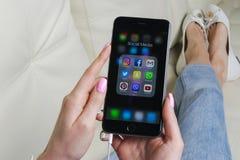 Kobieta Wręcza używać iphone 7 z ikonami ogólnospołeczny medialny facebook, instagram, świergot, Google zastosowanie na ekranie S Zdjęcie Stock