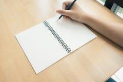 Kobieta wręcza writing na książce w biurze Biznesowa kobieta pracuje na biurku drewno Obraz Stock