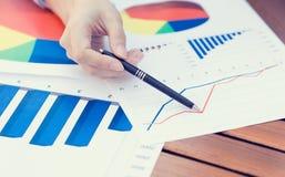 Kobieta wręcza wskazywać z piórem przy biznesową pieniężną raportową grafiką Zdjęcia Stock