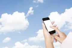 Kobieta wręcza mienia smartphone na niebie Fotografia Stock