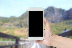 Kobieta wręcza przedstawieniom mobilnego smartphone w pionowo pozyci, blurre Zdjęcia Royalty Free