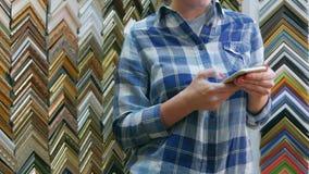 Kobieta wręcza texting na smartphone w ramowym atelier Zdjęcia Royalty Free