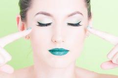 Kobieta wskazuje ona oczy jest ubranym fachowego wspaniałego makijaż Obraz Royalty Free