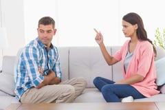 Kobieta wskazuje przy mężczyzna podczas gdy siedzący na kanapie Zdjęcia Stock