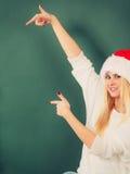 Kobieta wskazuje przy zieleni ścianą w Santa kapeluszu Obraz Royalty Free