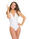 Kobieta wskazuje up na kopii przestrzeni w swimsuit fotografia stock