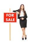 Kobieta wskazuje w kierunku a dla sprzedaż znaka Zdjęcie Royalty Free