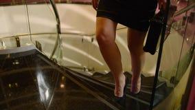 Kobieta wspina się schodki w sukni z walizką zbiory