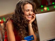 Kobieta wybiera Bożenarodzeniowych prezenty na laptopie z kredytową kartą Zdjęcie Royalty Free