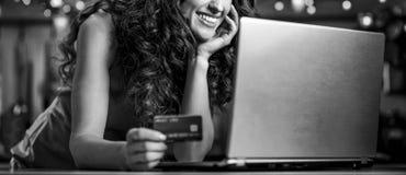 Kobieta wybiera Bożenarodzeniowych prezenty na laptopie z kredytową kartą Obraz Royalty Free