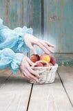 Kobieta wybiera brzoskwinie od łozinowego kosza Zdjęcie Royalty Free