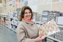 kobieta wybiera ceramiczną płytkę w sklepie obrazy stock