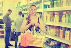 Kobieta wybiera detergent przy gospodarstwo domowe towarów supermarketem Zdjęcie Stock