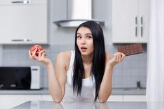 Kobieta wybiera jabłka lub czekolady na diecie zaskakiwał patrzeć obrazy royalty free