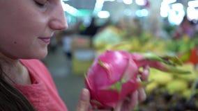 Kobieta wybiera jeden dojrzałą smok owoc i stawia je w zakupy koszu, Żeński klient przy owoc na rynku, zakończenie w górę zbiory wideo