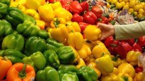 Kobieta wybiera kolorów żółtych pieprze w sklepie spożywczym zbiory